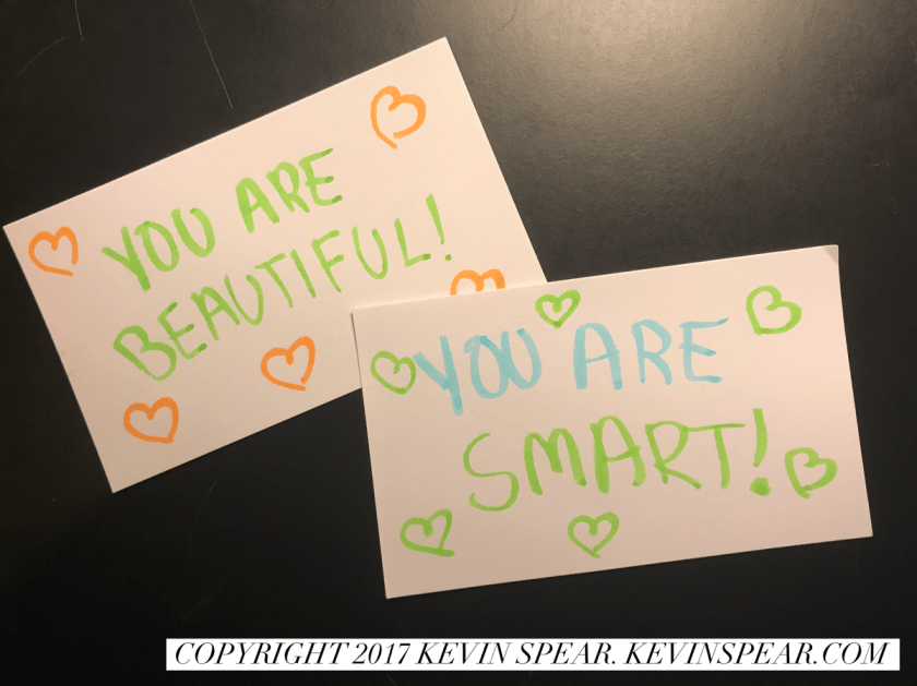 "Two note cards. One says, ""You are beautiful!"" The other says, ""You are smart!"""