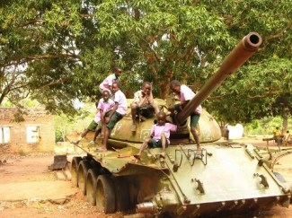 Children playing on an abandoned tank in Mundri, South Sudan. Huffington Post.