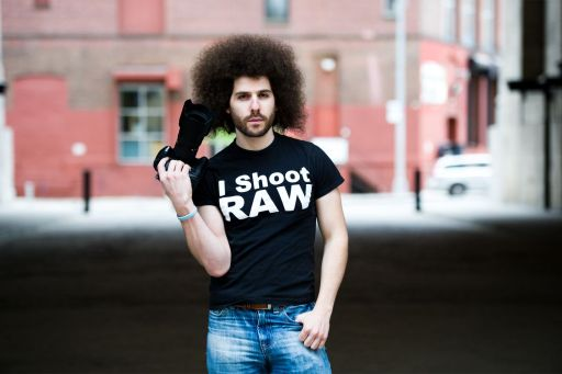 "An image of pro photographer Jared Polin holding a camera, and wearing one of his signature, ""I Shoot RAW"" t-shirts."