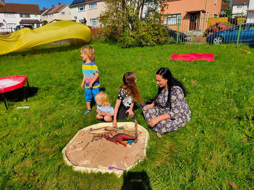 A woman with dark hair and three children with fair hair play with dinosaurs in a sand pit.