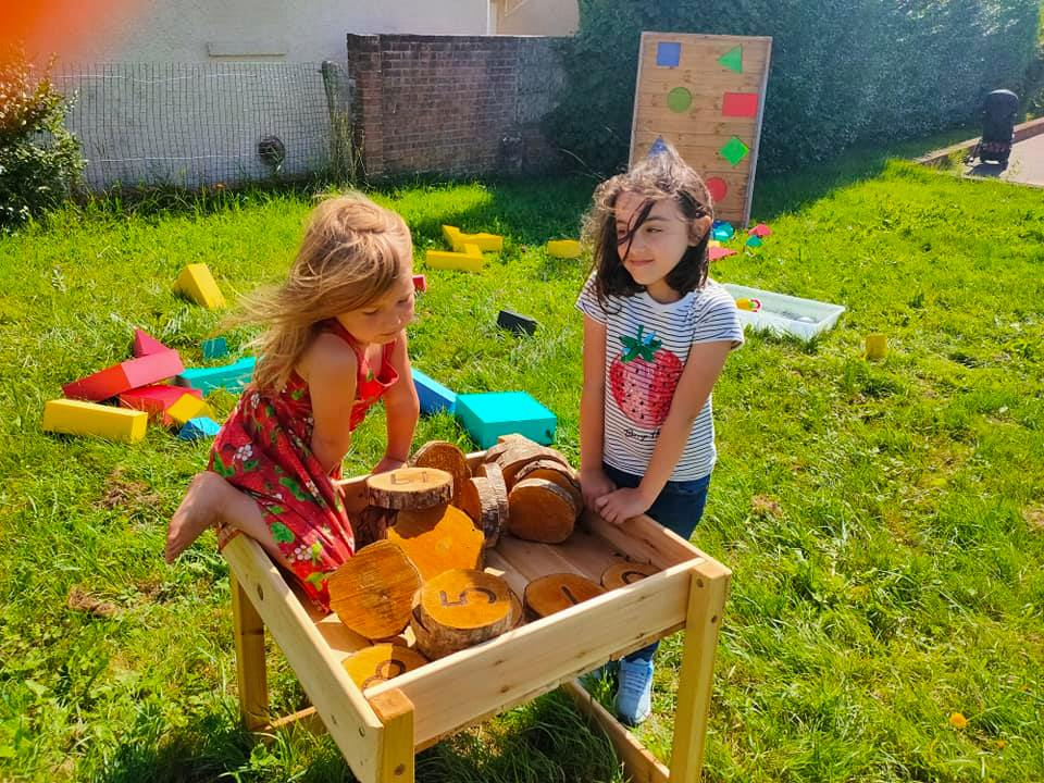 Two young girls play with log slices to learn numeracy skills