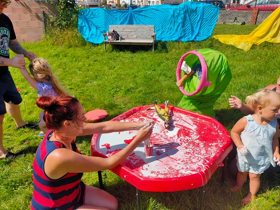 grown ups and children playing with gunge and dinosaurs in the sun