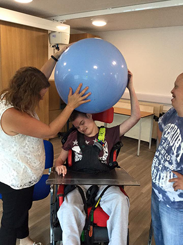 Support workers assist a young man in a wheel chair to enjoy playing with a large, blue inflated exercise ball