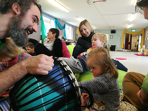 dave of keycreate holds a djembe drum infront of a young girl with additional needs so she may play it