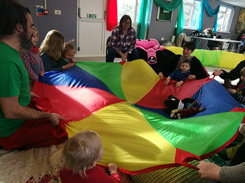 a group of children and adults flutter a multicoloured parachute as they sit around it in a circle to shake the toys that are on top of it.