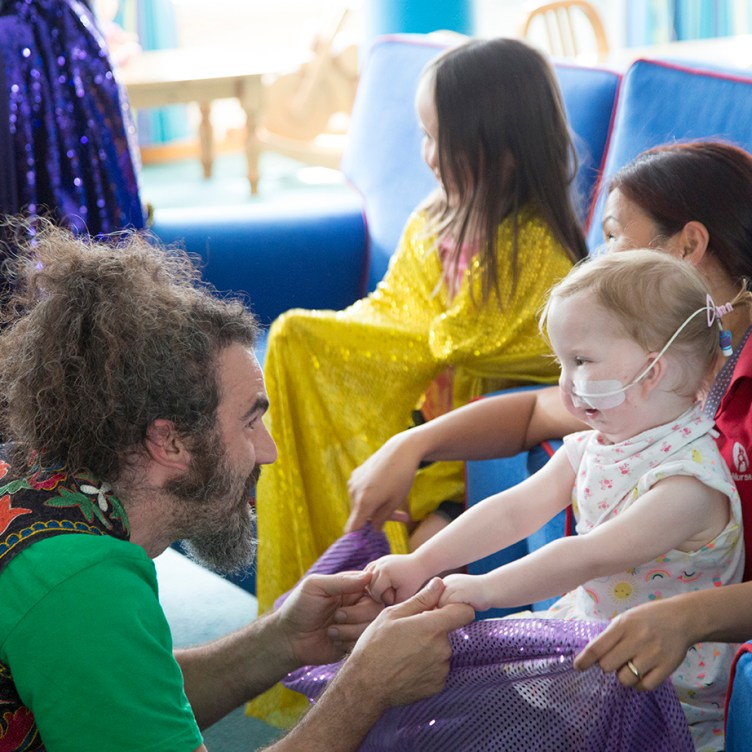 KeyCreate's Dave holds hands and sings to a smiling young girl at a hospice who has a feeding tube