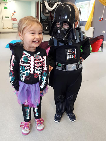 a young girl is dressed as a skeleton witch, stood next to a boy dressed as darth vader from lord of the rings for halloween.