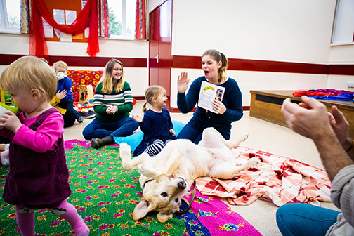 A female author and her dog, the subject of her book, tell their story to a circle of children seated in playgroup.