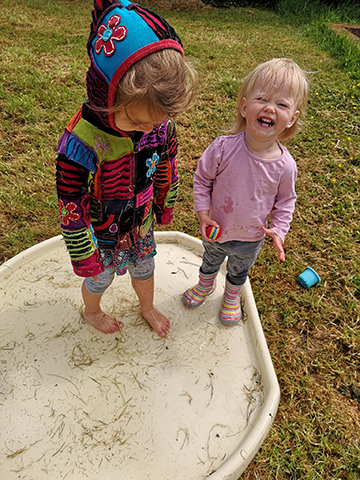two young girls stand in a water tray laughing. One wears wellies, the other has bare feet.