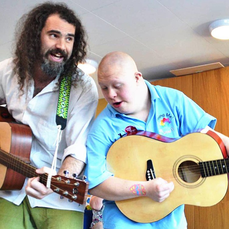 KeyCreate's Dave and a volunteer lean into each other to each play an acoustic guitar and sing during a workshop