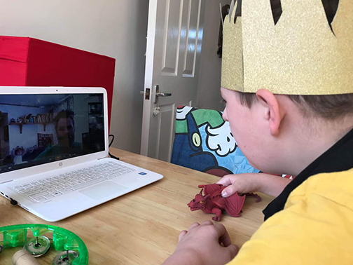 A young boy sitting in front of a laptop, wearing a party hat while participating in a live one to one zoom play session.