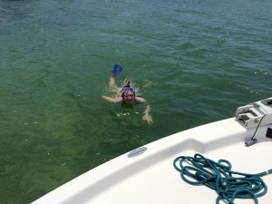 girl swimming to boat