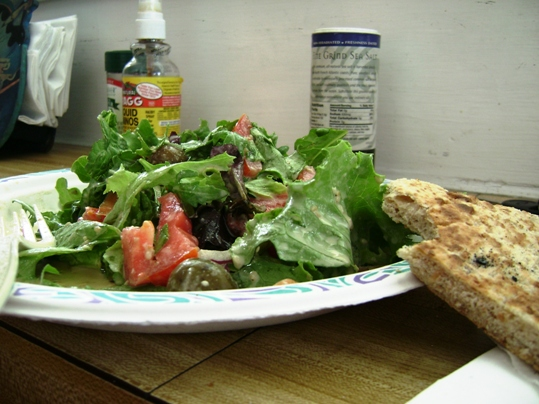 A plate of food with a sandwich and a salad - Spinach salad