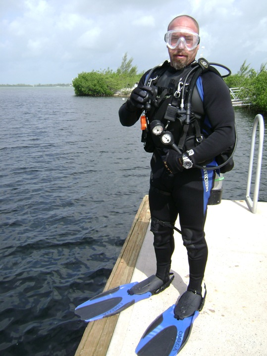 A person standing next to a body of water - Dry suit