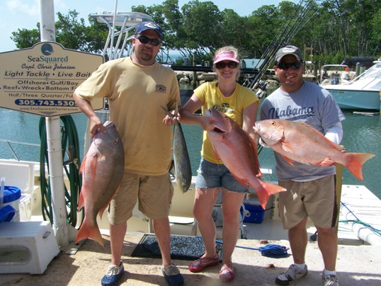 A group of people standing next to a man holding a fish - Fishing