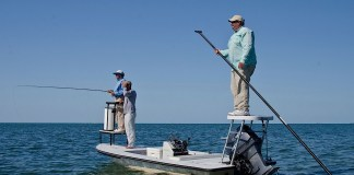A couple of people on a boat in the water - Recreational fishing