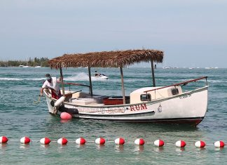 A red and white boat sitting next to a body of water - Fish 'n Fun Boat & Watersports Rentals