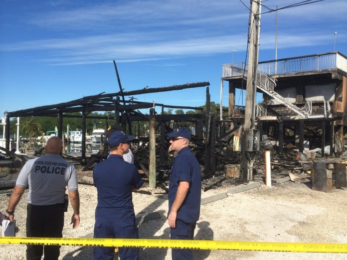 Investigators inspect the damage at Salty's Bar & Grill late Saturday morning. Two boats were destroyed in the fire. A car in the parking lot of the restaurant also burned. JASON KOLER/The Weekly