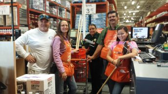 Jerry Diegez, left, and Sgt. Linda Mixon, center, pose with The Home Depot employees and the gratis supplies.