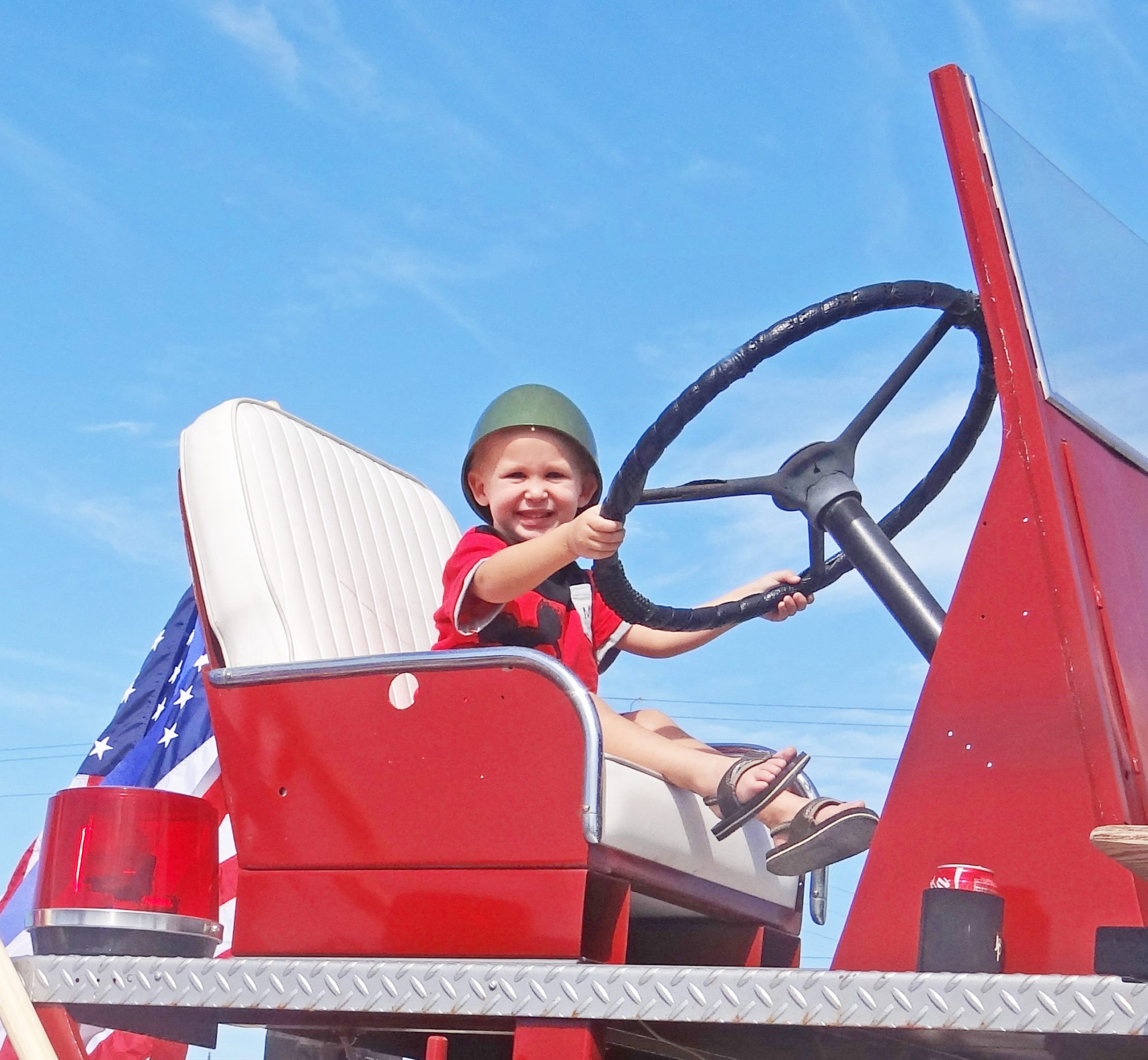 This little dude looks pretty happy at the wheel of the old fire truck.