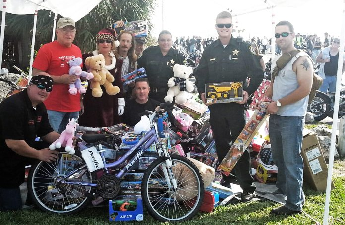 #News: Toy drive for needy kids coming to an end - A group of people standing next to a bicycle - Mountain bike