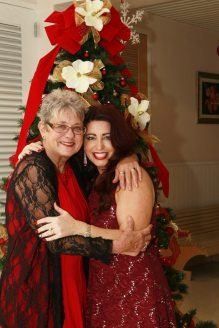 Sally Mishmash and Shawnabel Massaro greet each other in front of a fabulous tree.