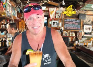 #Libation: Hogfish Bar and Grill - A man holding a sandwich in a restaurant - Beer