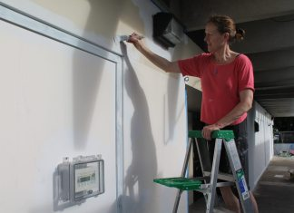 #News: Artist paints mural at Montessori - A man standing in front of a refrigerator - Jean Sport Aviation Center