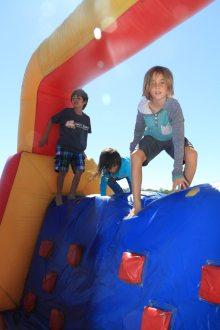 Cody leaps across the bounce house.
