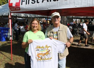 #Seen Around Town: Seafood Festival was profitable for great cause - A person holding a sign - Car