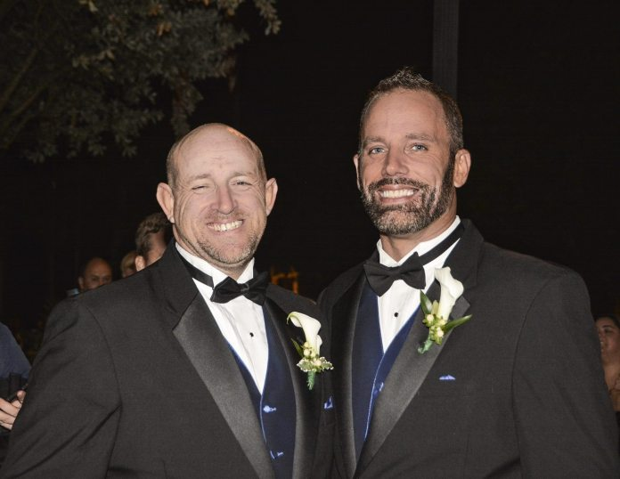 First Same-Sex Wedding Expo Set for Key West - A man wearing a suit and tie - Gourmet Nibbles & Baskets & Flowers