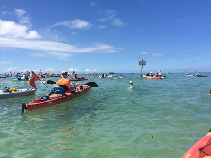 Swimming around Key West … is much easier for the kayaker - A group of people on a boat in the water - Sea kayak
