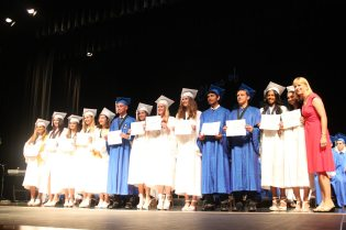 Grads receive awards – Scholarships further seniors' education goals - A group of people performing on stage in front of a crowd - MARATHON MIDDLE HIGH SCHOOL