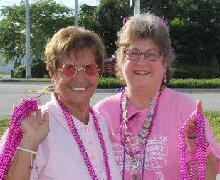 Toni Appell, left, and Michelle Iarocci hand out the pink bead necklaces.