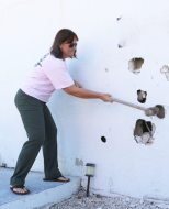 Local Mote friend Dolly Garlo takes a swing at the old building before it is demolished.