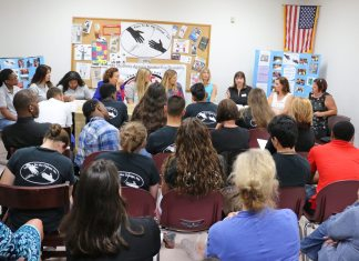 Teens host town hall meeting - A group of people in a room - Public Relations