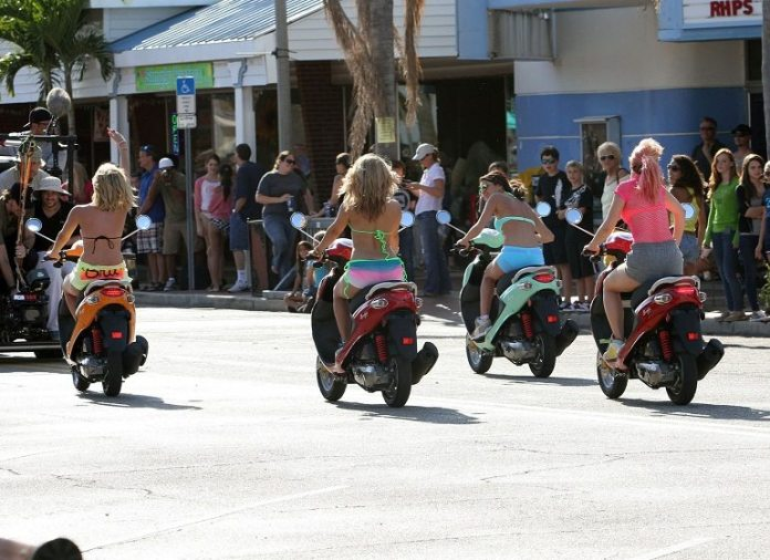 ON TWO WHEELS: Death and injury in Key West - A group of people riding on the back of a motorcycle - Scooter