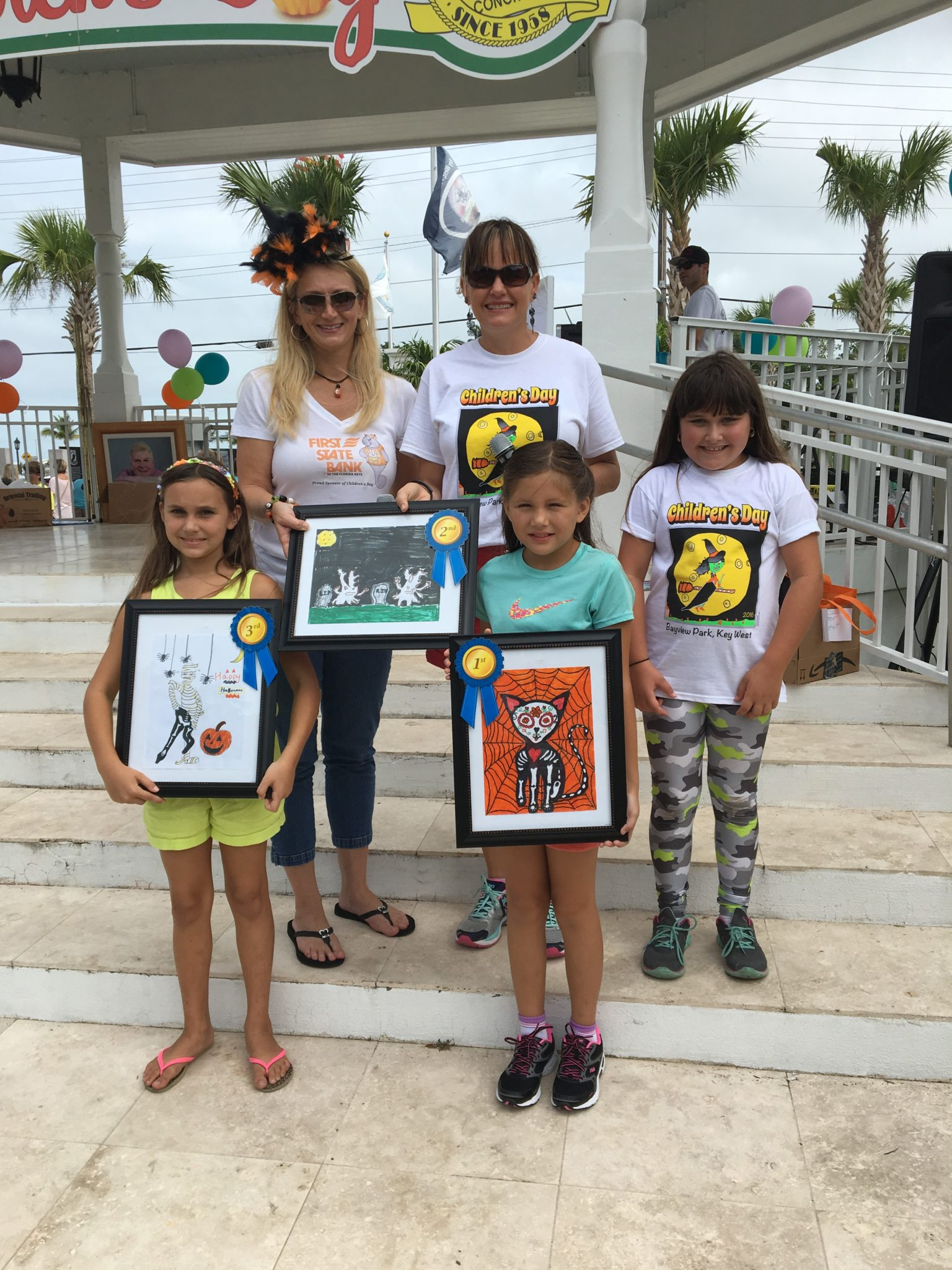 Ava Rivera, 8, right, sports her winning 2016 design for this year's Children's Day. The 2017 t-shirt contest winners are also pictured. Next year's shirts will show the Day of the Dead cat with spider web background.