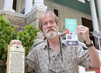 Tour in hand: Free app puts history at fingertips - A person holding a sign in front of a building - Tree