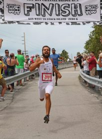 Moosain Bolt, aka Matt Hiemstra, comes across the bridge in a lighting 14 seconds, setting a new Cow Key Bridge Run record.