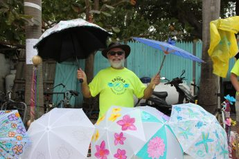Dr. Jim Gerbraecht happily sells parasols raising even more money for the Bahama Village Music program.