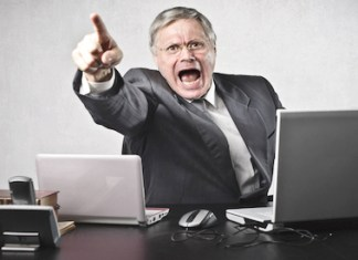 Top ways to make your boss angry - A person sitting at a desk with a laptop and smiling at the camera - Leadership