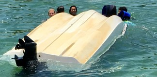 Local rescues 5 children from capsized boat - A group of people swimming in the water - Florida Keys