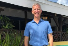 "Charles ""Chuck"" Licis works  tirelessly for Take Stock - A man in a blue shirt standing in front of a building - Florida Keys"