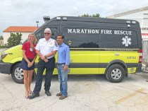 State Rep. Holly Raschein, left, Marathon Fire Chief John Johnson and U.S. Rep Carlos Curbelo pose in front of one of the city's new fire rescue vehicles.