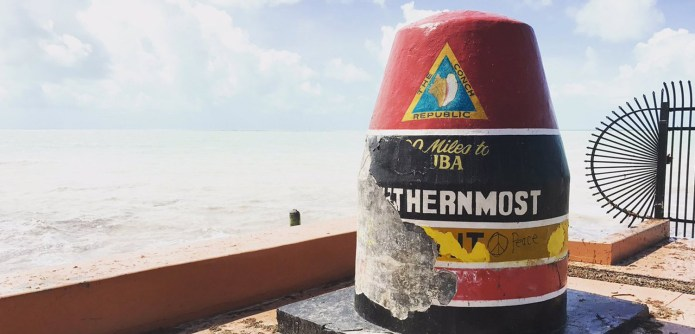 AN AMAZING 'SLIDE SHOW' - A sign on a beach with Southernmost point buoy in the background - Southernmost Point of the Continental US