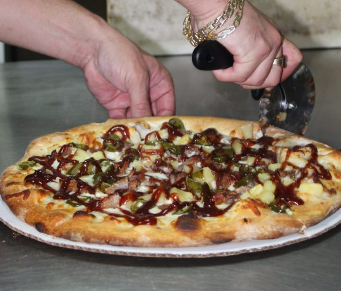 That's amore – Under new ownership, Driftwood Pizza soaring to new levels - A person cutting into a pizza - Pizza