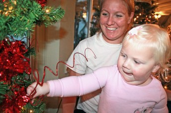 Avery, 1, helps mom Chelsea Lyons put the sparkle on the upside-down tree sponsored by Coral Construction.