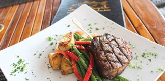 Weekly EATS:  Snooks Bayside Keeps the Vibe Alive - A plate of food with a fork and knife - Beef tenderloin