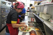 Hot pizza, saucy wings at Key Largo pizzeria - A person preparing food in a kitchen - Pizza